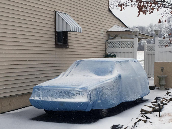 An original K car wagon sits under snow and a car cover this morning